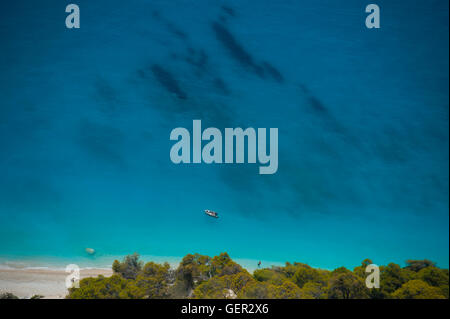Greece: Egremni beach on Lefkada from above with a small boat and a lone swimmer - Stock Photo