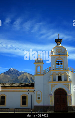 A Catholic Church in Quiroga, Ecuador with the volcano, Mount Cotacachi in the distance - Stock Photo