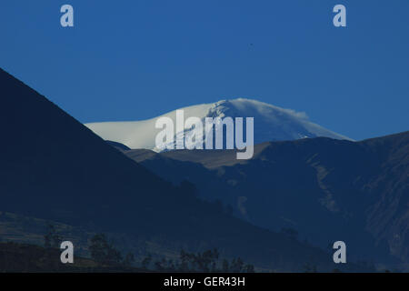 The snow covered peak of the volcano, Mount Cayambe, in the Andes Mountains near Cotacachi, Ecuador - Stock Photo