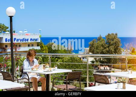 BALI, GREECE - APRIL 28, 2016: Elderly woman in blue shirt is having lunch on veranda of restaurant, overlooking - Stock Photo