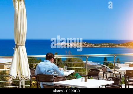 Young man in blue shirt is having lunch on veranda of restaurant, overlooking the Cretan sea. Resort hotel Atali - Stock Photo
