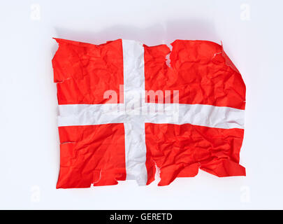 A crumpled and torn paper Dannebrog flag, the Danish flag. Close to being the happiest people? - Stock Photo