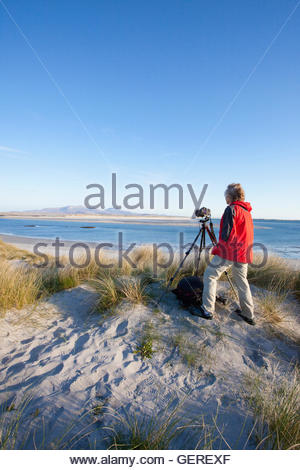 A wildlife photographer with a camera and tripod  in the dunes above the white sandy beach at, Isle of Benbecula, - Stock Photo
