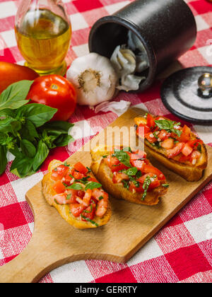 Photo of Italian bruschetta on a wooden board with the ingredients behind. Focus across the middle. - Stock Photo