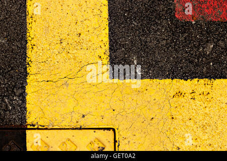 Asphalt painted yellow and red, suitable for textured abstract background. Horizontal image.