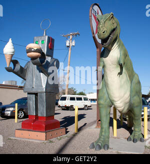 Robot holding an ice cream cone and hamburger and dinosaur outside a restaurant in Hatch New Mexico - Stock Photo