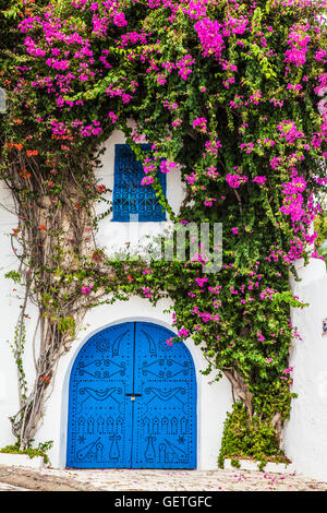 A typical blue studded wooden door with bougainvillea growing up the whitewashed wall and wrought iron window dressing - Stock Photo