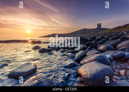 Dunstanburgh castle in Northumberland above the famous boulders in Embleton Bay. - Stock Photo