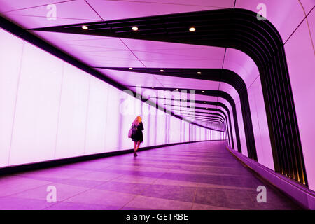 A young woman walks along the illuminated lightwall corridor connecting One Pancras Square with King's Cross underground - Stock Photo