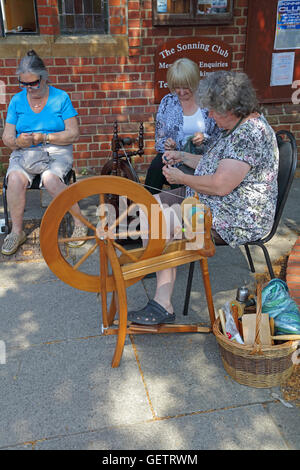 Two ladies sitting by their spinning wheels 'teasing' out the wool ready to go onto the spinning wheel to make yarn. - Stock Photo