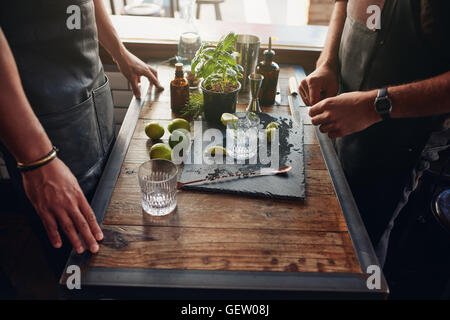 Close up shot of two male barmen preparing new cocktail recipe. Bartenders standing with accessories and ingredients - Stock Photo