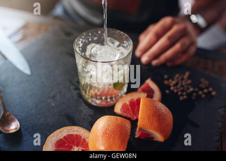 Closeup shot of bartender pouring drink into a glass full of ice cubes with cut grapefruits and peppercorn on counter. - Stock Photo
