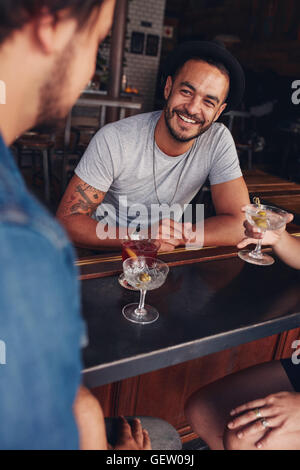 Happy young caucasian man sitting at a coffee shop with his friends. Young friends sitting at a cafe table having - Stock Photo