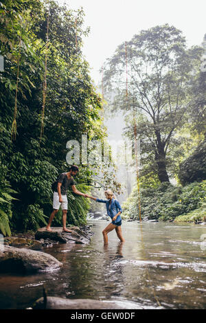 Outdoor shot of young man helping woman crossing stream. Couple in forest crossing the creek. - Stock Photo