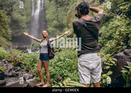 Excited young woman standing in front of a waterfall being photographed by her boyfriend. Photographer taking pictures - Stock Photo
