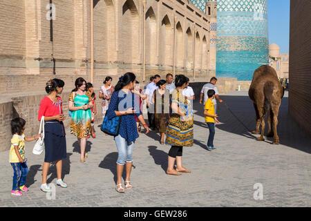 People look at the camel in Khiva, Uzbekistan. - Stock Photo