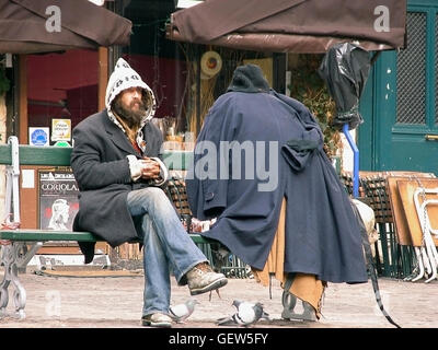 Eccentric character sitting on bench in Place du Marché Ste-Catherine, le Marais, Paris, France - Stock Photo