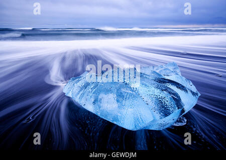 Waves washing around a small iceberg on the beach at Jokulsarlon in Iceland. - Stock Photo