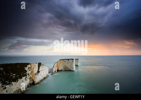 A stormy sunrise over Old Harry Rocks near Swanage in Dorset. - Stock Photo