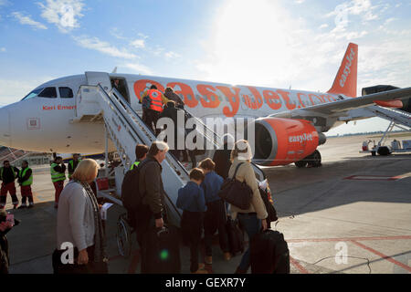 Passengers using the front aircraft stairs to board an Easyjet aircraft. - Stock Photo
