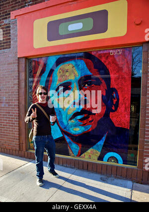 Man showing the peace sign in front of an Obama Hope mural. - Stock Photo