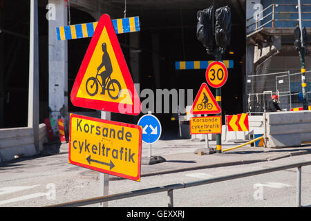 Warning roadsigns along urban road. Swedish text means intersecting bicycling - Stock Photo