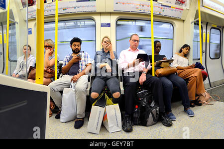 London, England, UK. People on the Tube / underground, all looking at mobile phones / iPads - Stock Photo