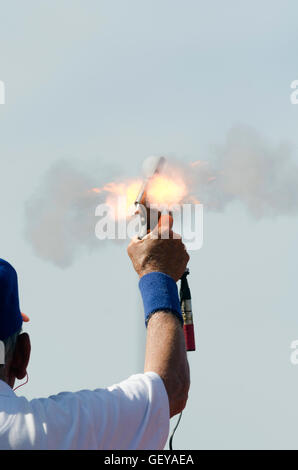 Official fires starting pistol at beginning of track and field event - Stock Photo