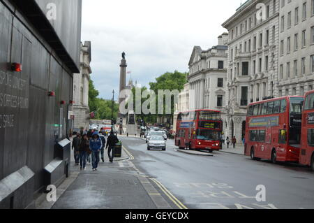 London Street view with the characteristic London double decker red buses. - Stock Photo