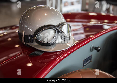 Helmet and glasses resting on a luxury convertible sports car. - Stock Photo