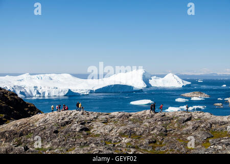 People on a hiking trail at Nakkaavik viewpoint overlooking Disko Bay with icebergs from Ilulissat Icefjord offshore. - Stock Photo