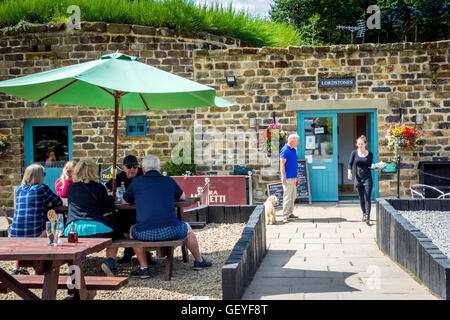 A family group enjoying sunshine, a man with a dog and a waitress carrying tea at Lord Stones café North Yorkshire - Stock Photo