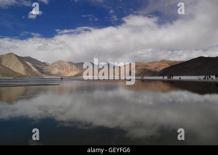 A play of light and dark along with curious cloud formation reflected on the Pangong Tso - Stock Photo