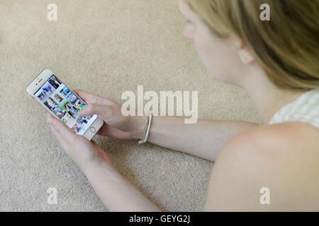 Teenage girl using Instagram social media app on her mobile phone (iphone) - Stock Photo