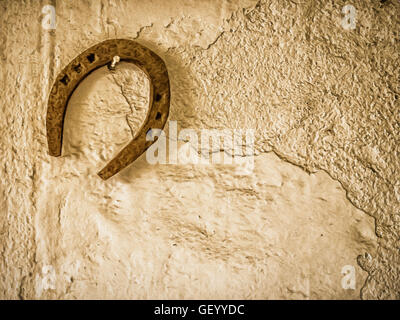 Horseshoe hanging on a wall in a barn in a farm - Stock Photo