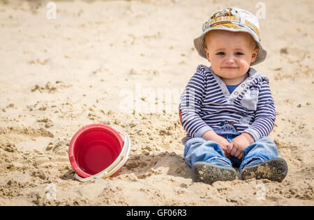 Cute little boy sitting in a sandpit in an outdoor playground - Stock Photo