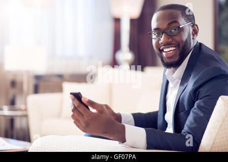 Man looking at camera and holding phone - Stock Photo