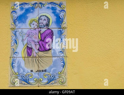 Porcelain plaque depicting the Holy Family on the wall above door in the Ponta Delgada town in Sao Miguel, Azores, - Stock Photo