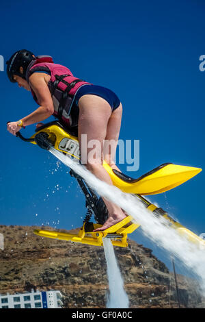 Woman hovering above water on a jet ski in Gran Canaria, Spain. Picture taken 8 May 2015. - Stock Photo