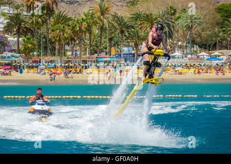 Woman hovering above water on a jet ski in Gran Canaria, Spain. Picture taken on the 8th May 2015. - Stock Photo