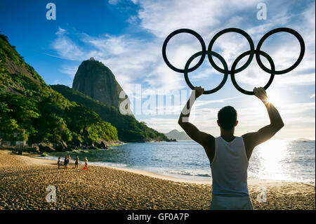 RIO DE JANEIRO - OCTOBER 31, 2015: Athlete holds Olympic rings in front of a sunrise silhouette of Sugarloaf Mountain. - Stock Photo