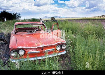 faded red vintage car in a field near Seligman Arizona - Stock Photo