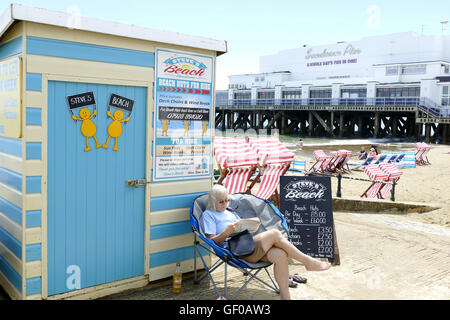 Sandown, Isle of Wight, UK. June 21, 2016. A young lady sits prepared to take hire of beach huts and deck chairs - Stock Photo