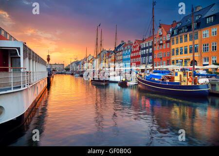 Copenhagen, Nyhavn Canal. Image of Nyhavn Canal in Copenhagen, Denmark during beautiful sunset. - Stock Photo