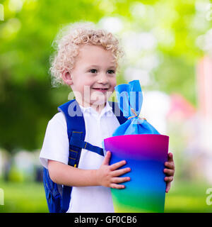 Happy child holding traditional German candy cone on first school day. Little student with backpack excited to be - Stock Photo