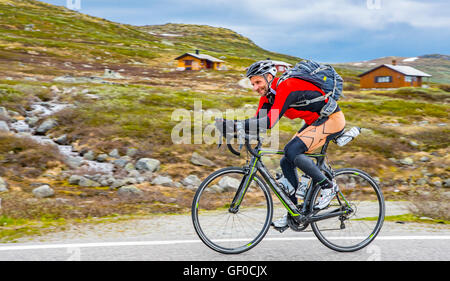 Cyclist peddling on route 7, Hardangervidda National Park in springtime. Norway, Hordaland, Scandinavia, European - Stock Photo
