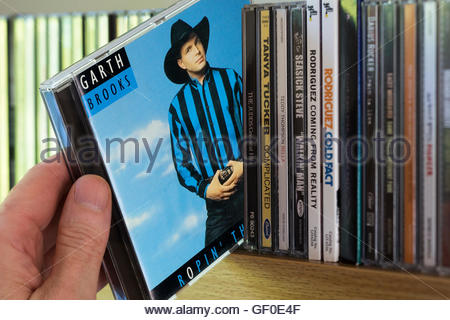 The 1991 Garth Brooks album, Ropin' the Wind, CD being chosen from other CD's on a shelf - Stock Photo