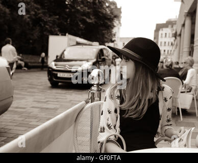 Young 12 year old girl wearing Fedora hat and looking to the side in a natural way. Sitting at table in a road side - Stock Photo