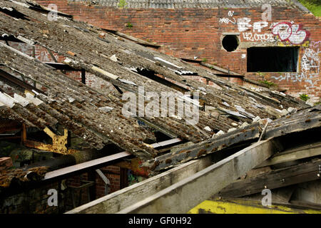 Damaged corrugated asbestos roofing on abandoned industrial building. - Stock Photo