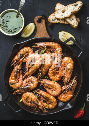 Roasted tiger prawns in iron grilling pan on wooden board with fresh leek, lemon slices, pepper, bread and pesto - Stock Photo